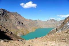 Lac vert mountain entouré par des montagnes Photographie stock