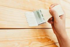 Laca de la pintura del cepillo del uso de la mano del primer en la superficie de madera Fotografía de archivo libre de regalías