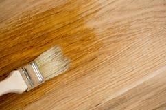 Laca del claro de la pintura del cepillo del uso de la mano del primer en la superficie de madera Foto de archivo libre de regalías