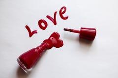 Laca roja Amor - escrito en esmalte de uñas rojo en un fondo blanco Billete para una postal - día de fiesta del lacomanyak Imágenes de archivo libres de regalías