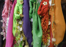 Lace. Beautiful silk scarves for sale at a festival with gold and silver coins Royalty Free Stock Photography