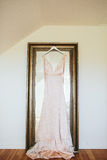 Lace Bohemian Wedding Dress. Champagne pink satin lace wedding dress hanging on a large mirror on a wedding day morning in a bridal suite Stock Photo