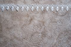 Lace border. White lace border on a beige cement background royalty free stock photo