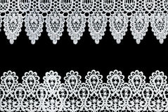 Lace Borders. White lace forms a delicate border against black background royalty free stock images