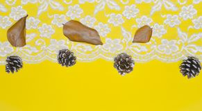 Lace borders and acorns against a yellow background as a concept of changing seasons, Christmas. Blurred on purpose Christmas theme with space for text and royalty free stock photography