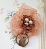 Lace brooch. Hand made lace brooch with a bird and decorative nest pendant on a floral background stock image