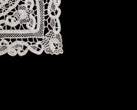 Lace Corner. Corner of a piece of lace from Burano, Italy - on a black background stock photos