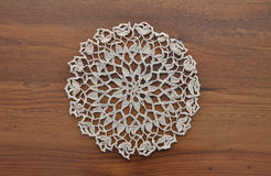 Lace doily on dark wood Stock Photo