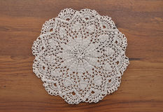 Lace doily on dark wood Stock Image