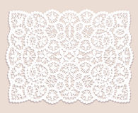 Lace doily. White lace doily with flowery pattern on a beige background Stock Photo
