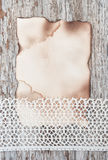 Lace fabric and aged paper on the old wood Royalty Free Stock Photo