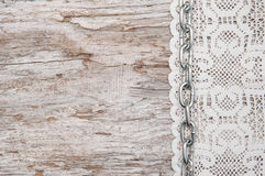 Lace fabric with chain on the old wood Stock Images