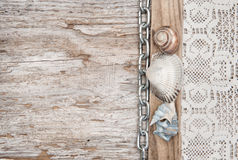 Lace fabric with chain and seashells on old wood Stock Photos