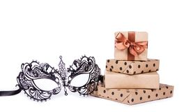 Lace mask and gifts. Metal masquerade mask and stack of gifts. Gift boxes on white background. Mask on white background royalty free stock photo
