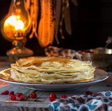 Lace pancakes and cherry on the table. Pancake week stock photo