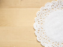 Lace paper on wooden table Royalty Free Stock Photography