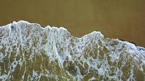 Lace pattern on the sand leave by waves. Aerial survey. Slow motion. Lace pattern on the yellow sand of white foam leave by transparent waves. Aerial survey stock video footage