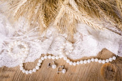 Lace, pearl necklace, earrings and ears of corn, rustic Stock Photography