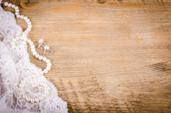Lace, pearl necklace, earrings on wooden background, rustic Stock Images