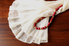 A lace petticoat with a coral necklace on a brown, wooden table. A white, lace petticoat and a red coral necklace with golden spheres on a brown wooden table Stock Images