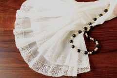 A lace petticoat with a pearl necklace on a brown, wooden table. A white, lace petticoat and a black and white pearl necklace on a brown wooden table Royalty Free Stock Photos