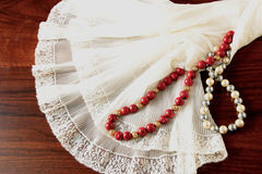 A lace petticoat with a pearl necklace and a coral necklace on a brown, wooden table. A white, lace petticoat, a grey and white pearl necklace and a red coral Stock Image