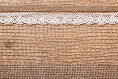 Lace ribbon on burlap cloth background Stock Image