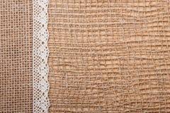 Lace ribbon on burlap cloth background Royalty Free Stock Image