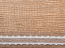 Lace ribbon on burlap cloth background Royalty Free Stock Photography
