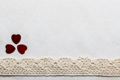 Lace ribbon hearts on white cloth. Royalty Free Stock Photos
