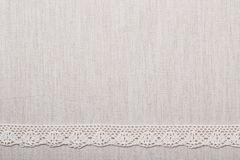 Lace ribbon on linen cloth background. Lace ribbon on natural linen, bright cloth fabric background. Border frame Stock Photography