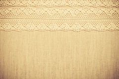 Lace ribbon on linen cloth background Stock Photos