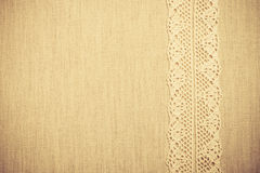 Lace ribbon on linen cloth background Royalty Free Stock Image
