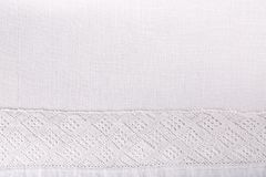 Lace ribbon on white linen fabric texture as a border frame. Cloth background. Rustic style royalty free stock photos