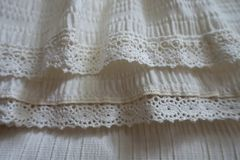 Lace ribbons stitched to frills on hem of skirt Royalty Free Stock Photo