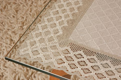 Lace tablecloth on a glass table Stock Photography
