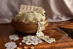 Lace tape in a wicker basket on the table. Fringe or lace tapes in a wicker basket royalty free stock photo