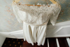 Lace top wedding dress hanging. Near the wall Stock Images