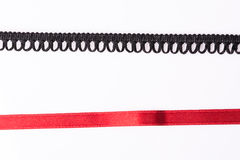 Lace trim ribbon over white. Black and red Royalty Free Stock Image
