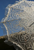 Lace umbrella against the blue sky Stock Image