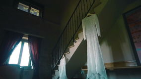 Lace wedding dress hanging on ladder in antique room. Pan stock video