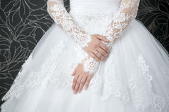 Lace white wedding dress with long sleeves. Women's hands Royalty Free Stock Photo