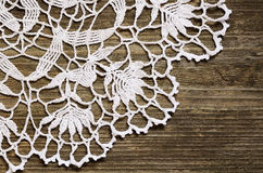 Lace on wood. Crochet lace on an old weathered wood royalty free stock image
