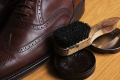 Laced brown leather classic Brogue shoes with polishing cream and brush Royalty Free Stock Images