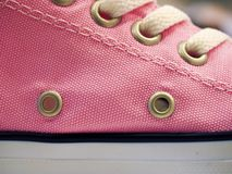 Laced pink trendy sneakers with grommets, close up stock photos