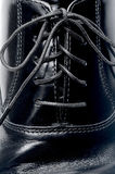 Laces on a black leather shoe Stock Images