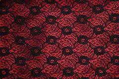 Lacet noir sur le satin rouge Photographie stock libre de droits