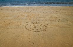 Lachebekje met erachter overzees, in het gouden zand dat van weinig wordt getrokken stock fotografie