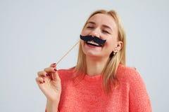 Lachen blond mit dem gefälschten Schnurrbart Stockfotografie