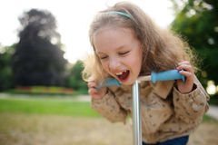 Lachen Lttle-Mädchens nett, das an einem Rad des Rollers gelehnt wird Lizenzfreie Stockfotografie
